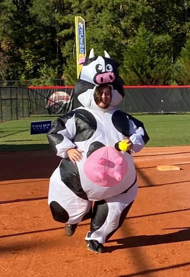 Emma Harlow runs the bases as a blow - up cow for costume practice.