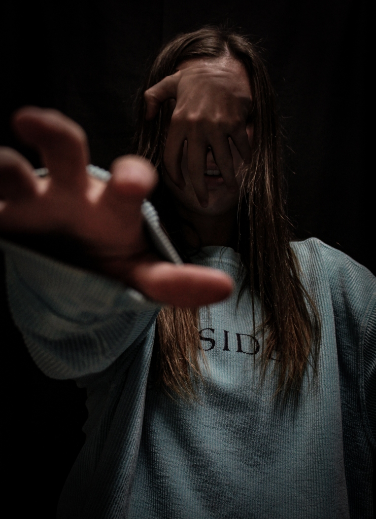 Photo 3 student, Meredith Rice, used Photoshop to blend a ghost hand onto the face. Additional lighting manipulation creates an especially chilling effect.
