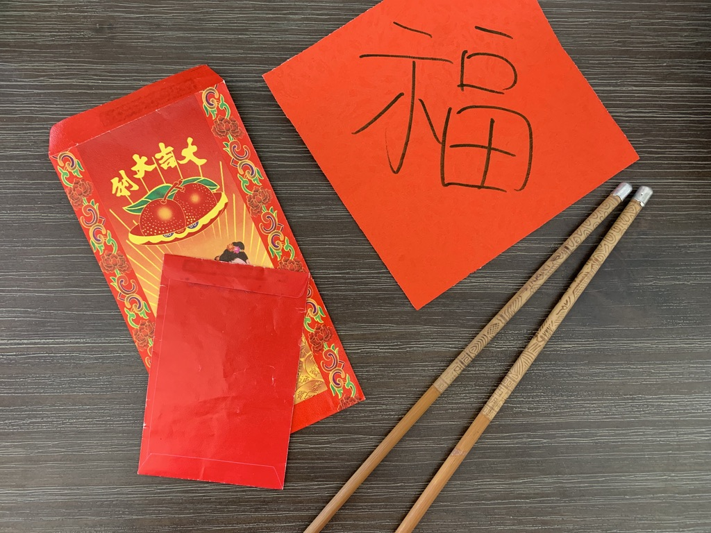 chopsticks red pockets and chinese character for luck on red paper